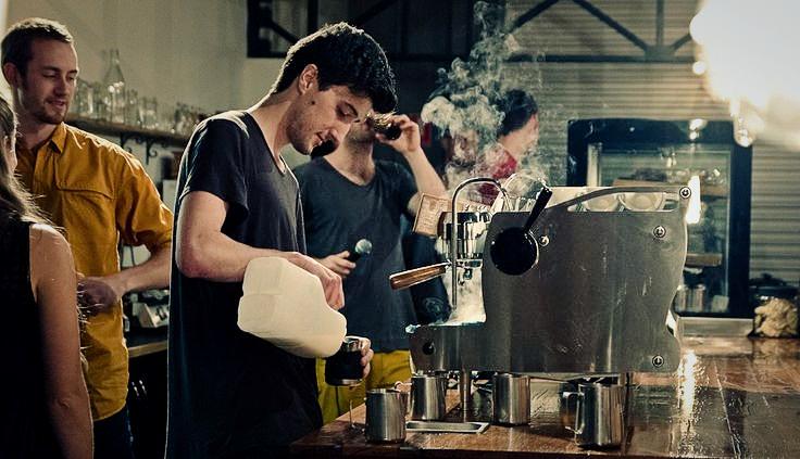 Seorang barista sedang membuat espresso menggunakan mesin espresso