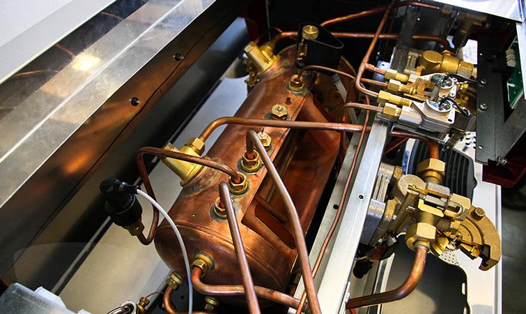 Bagian dalam mesin espresso: boiler dan heat exchanger.