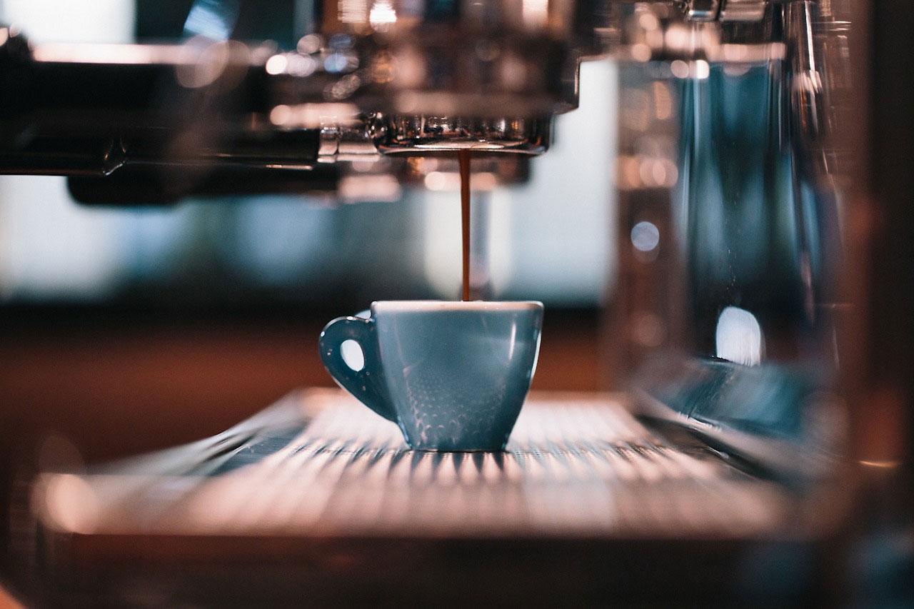 Secangkir espresso sedang dibuat dengan menggunakan mesin espresso