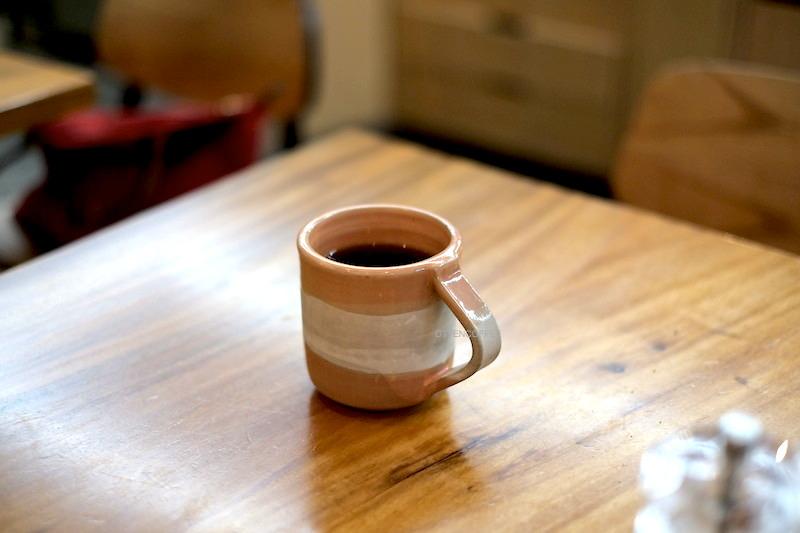 Cangkir cantik memeluk mesra kopi nikmat.